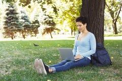 Vrouwenzitting op het gras met laptop in openlucht Stock Foto's