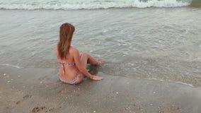 Vrouwenzitting op het strand dichtbij het warme overzees stock footage