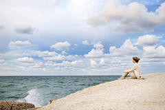 Vrouwenzitting op het strand die het overzees en de hemel bekijken Royalty-vrije Stock Fotografie