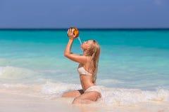 Vrouwenzitting op het witte het zandstrand van Zanzibar ` s Stock Foto