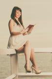 Vrouwenzitting op hindernis dichtbij overzees, lezingsboek Stock Afbeelding
