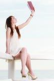 Vrouwenzitting op hindernis dichtbij overzees, lezingsboek Stock Afbeeldingen