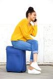Vrouwenzitting op koffer en het spreken op cellphone Royalty-vrije Stock Foto