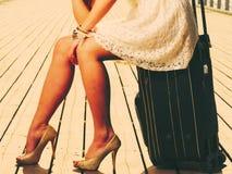 Vrouwenzitting op koffer, pijler op achtergrond royalty-vrije stock foto