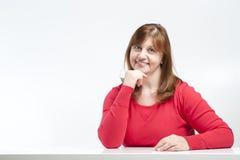 Vrouwenzitting op middelbare leeftijd met zijn ellebogen op de lijst stock afbeelding
