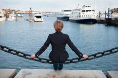 Vrouwenzitting op oceaan en pijler die denken dromen Mening van de rug royalty-vrije stock fotografie