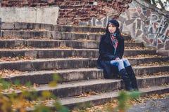 Vrouwenzitting op oude treden in de herfstpark Stock Fotografie