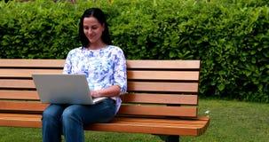 Vrouwenzitting op parkbank die laptop met behulp van stock video