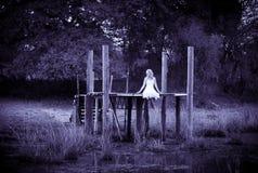 Vrouwenzitting op pijler naast stroom stock afbeeldingen