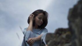 Vrouwenzitting op reusachtige rotsen stock video
