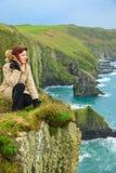 Vrouwenzitting op rotsklip die aan oceaanco. Cork Ireland kijken Stock Foto's