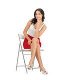 Vrouwenzitting op stoel stock fotografie