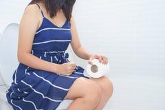 Vrouwenzitting op toilet met toiletpapier - constipatieconcept stock afbeeldingen