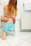 Vrouwenzitting op toilet in ochtend stock afbeeldingen