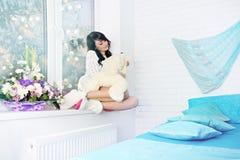 Vrouwenzitting op venstervensterbank Royalty-vrije Stock Afbeeldingen
