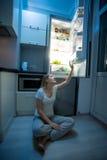 Vrouwenzitting op vloer en het bereiken voor voedsel van open refrigera Royalty-vrije Stock Foto's