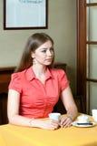 Vrouwenzitting in restaurant met kop koffie en blikken uit royalty-vrije stock foto