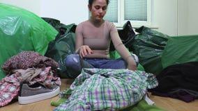 Vrouwenzitting in slordige ruimte en sorterende oude kleren stock videobeelden