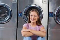 Vrouwenzitting tegen Wasmachines in Wasserij stock afbeeldingen