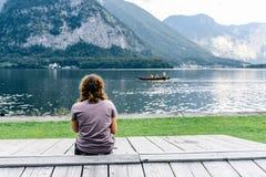 Vrouwenzitting terug op pijler bij oever van het meer stock afbeelding