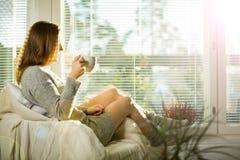 Vrouwenzitting thuis als voorzitter door het venster met kop van hete koffie royalty-vrije stock fotografie