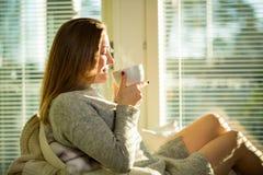 Vrouwenzitting thuis als voorzitter door het venster met kop van hete koffie stock foto