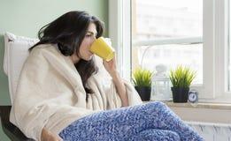 Vrouwenzitting thuis, in een algemene, het drinken thee wordt verpakt die stock afbeeldingen