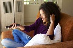 Vrouwenzitting thuis met afstandsbediening die op TV letten Royalty-vrije Stock Foto's