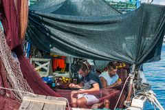 8 28 2012 Vrsar Хорватия 2 матроса очищают уловленных рыб Удить в Адриатическом море стоковое изображение