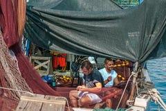 8 28 2012 Vrsar Kroatië Twee zeelieden herstellen het gescheurde netwerk op de boot Visserij in het Adriatische overzees royalty-vrije stock foto's