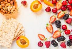 Vruchten, bessen en geheel korrel kernachtig brood op de witte marmeren ruimte van het lijstexemplaar Het concept het gezonde ete stock afbeelding