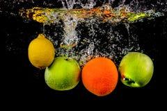 Vruchten de vlotter in water met bellen, het fruit is in waterplons en op een zwarte achtergrond geïsoleerd stock foto's