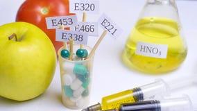 Vruchten In een glas met multi-colored pillen zijn platen met de code e-Supplementen Dichtbij zijn spuiten met nitraten, chemisch stock fotografie