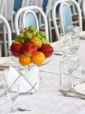 Vruchten in een vaas en een glaswerk op de lijst Stock Afbeeldingen