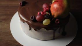 Vruchten en bessen bovenop cake stock video