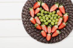 Vruchten en bessen op een wit hout Stock Afbeeldingen
