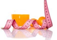 Vruchten en het meten van band op een witte achtergrond om een gezonde voeding te symboliseren Stock Foto's