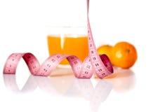 Vruchten en het meten van band op een witte achtergrond om een gezonde voeding te symboliseren Stock Fotografie
