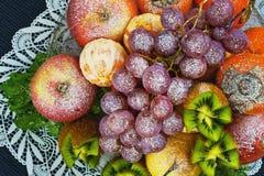 Vruchten met gepoederde suiker op een plaat op een blauwe achtergrond worden bestrooid die Royalty-vrije Stock Foto