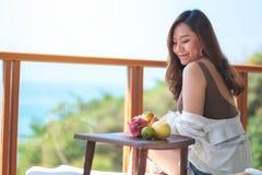 Vruchten van een de mooie Aziatische vrouwenholding terwijl geniet van zittend bij balkon stock foto