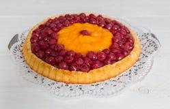 Vruchtencake met kersen en mandarijnen op wit hout Stock Afbeeldingen
