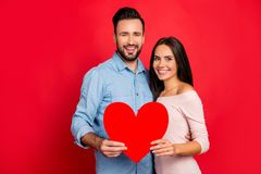 He vs she celebrating valentine day. Portrait of caucasian, beau. Tiful, lovely, cute, cheerful, positive couple holding red paper heart together standing over stock image