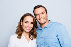 He vs she happy together. Close up portrait of confident, cute,. Adult, couple in casual outfit looking at camera standing over grey background Royalty Free Stock Photos