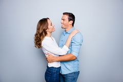 He vs she happy together. Close up portrait of cute, mature coup. Le in shirts, casual outfit hugging, looking to each other, standing over grey background Royalty Free Stock Image