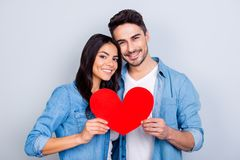 He vs she together forever. Love story of caucasion beautiful lo. Vely hispanic cute couple holding red heart together standing over grey background Stock Photography