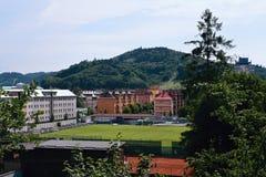 Vsetin Tjeckien - Juni 02, 2018: Fotbollfält mellan gamla hus i solig dag Arkivbild