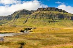 Västra isländskt berglandskap under en blå sommarhimmel. Royaltyfri Foto