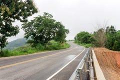 Våt huvudvägvägkurva bland träd med regnmolnet Arkivfoto