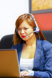 Vêtements et casque de port de bureau de jeune femme attirante se reposant par le bureau regardant l'écran d'ordinateur, fonction Photos stock