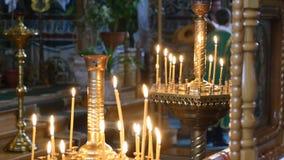 Vue à l'église du visage brûlant de bougies du Christ dans l'icône Léchez les bougies saintes de Lit de flamme Beaucoup de bougie banque de vidéos